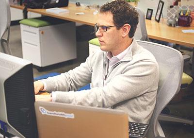 Man working at office desk as a truck broker
